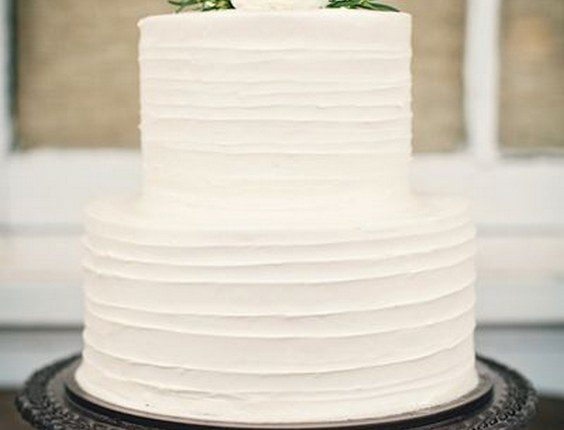 Simple white wedding cake with white flowers on top