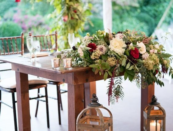 Wedding reception sweetheart table with wooden farm table, lanterns, candles