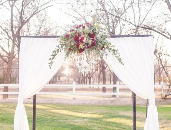 outdoor wedding ceremony arbor, ruby red flowers, draped white fabric, chandelier