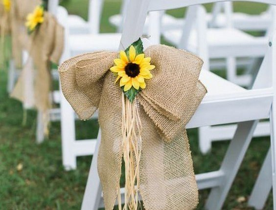 wite wedding chairs were paired with large burlap bows and sunflower