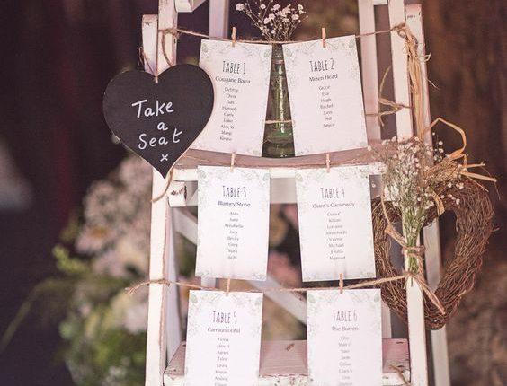 Retro wooden step ladder wedding table plan at barn wedding venue