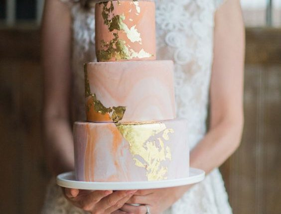 peach-colored wedding cake with gold accents
