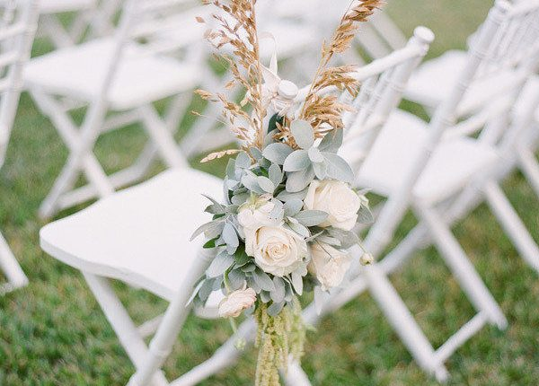 flower arrangement and pampas grass for wedding ceremony chairs
