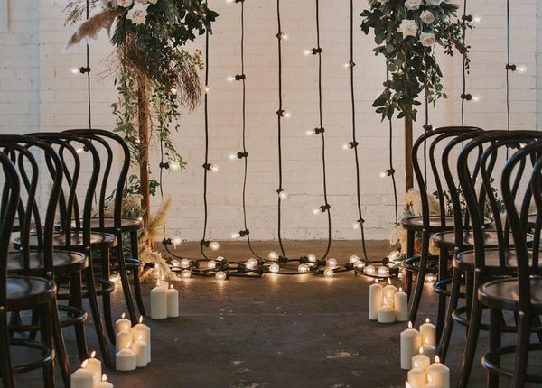 indoor floral wedding arch with pampas plumes and festoon lights