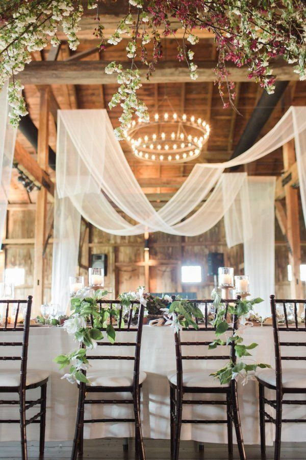 Rustic barn wedding reception space with draped fabric decor