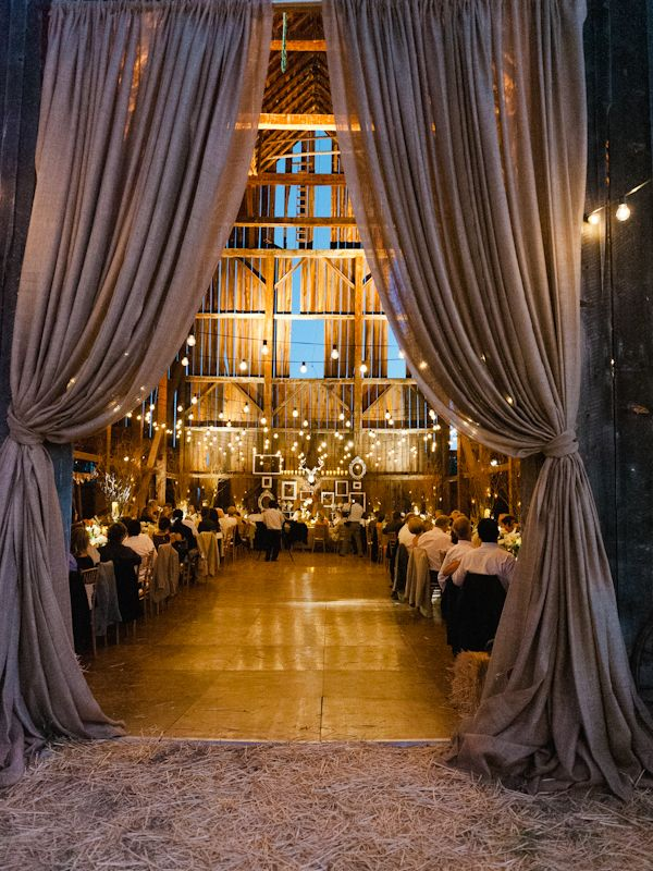 barn wedding decro with curtains, strung lights, candles, burlap