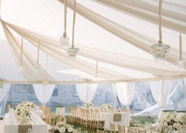 elegant ivory tent wedding reception with draping fabric