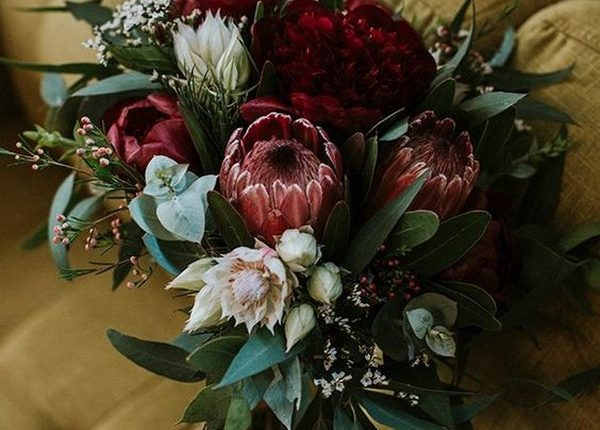 moody wedding bouquet with deep red proteas