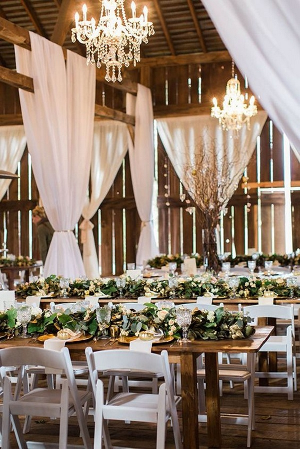 rustic barn wedding reception with greenery on wooden table