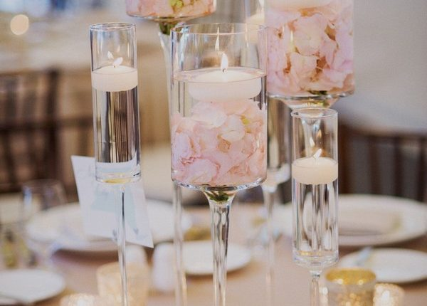 Clusters of stemmed hurricane vases filled with floating candles and rose petals