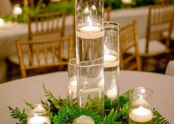 clear glass vases with floating candles displayed with ivory flowers + greenery