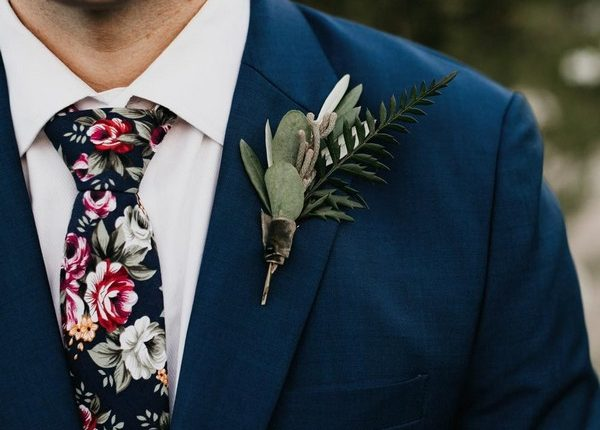 navy blue groom attire with floral tie and boutonniere
