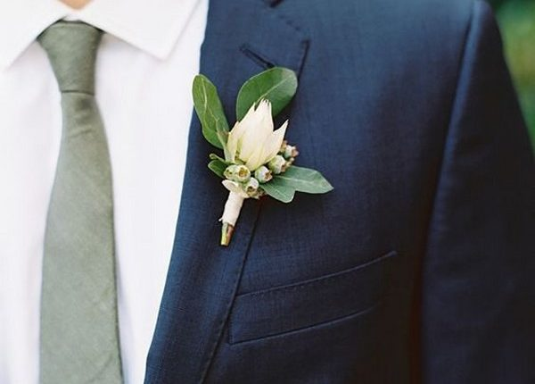 navy blue groom attire with green tie and boutonniere