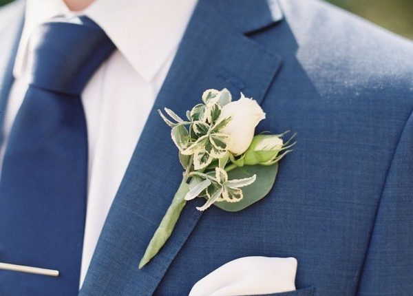 navy blue groom attire with navy tie and green boutonniere