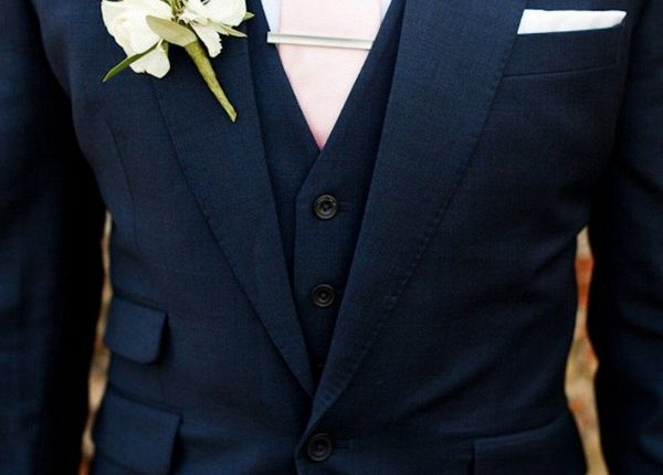 navy blue groom attire with pink tie and greenery boutonniere