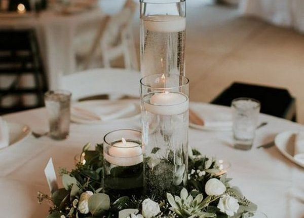 simple wedding centerpiece with candles and greenery