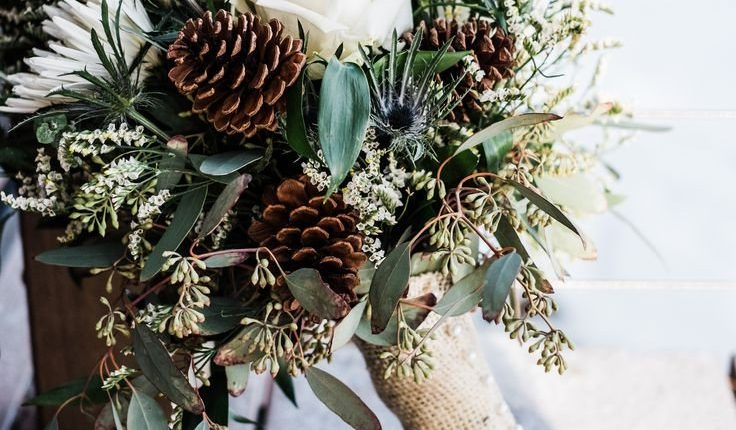 rustic winter wedding bouquet with white roses eucalyptus and pine cones
