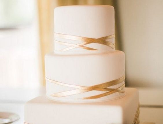 A three-tiered, square and round wedding cake with geometric gold stripes, from Cakes by Gina