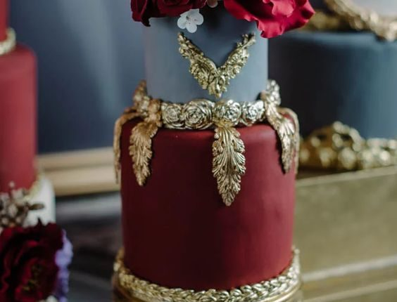 Deep red and pale blue wedding cake with baroque gold trim