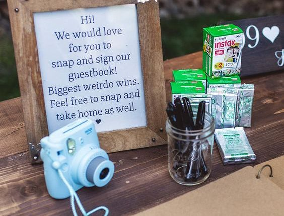 Place a Polaroid camera with film on a rustic table for an alternative approach to the wedding guest book