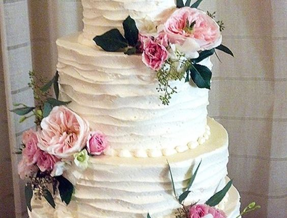 Rustic country old-fashioned wedding cake with pink flowers