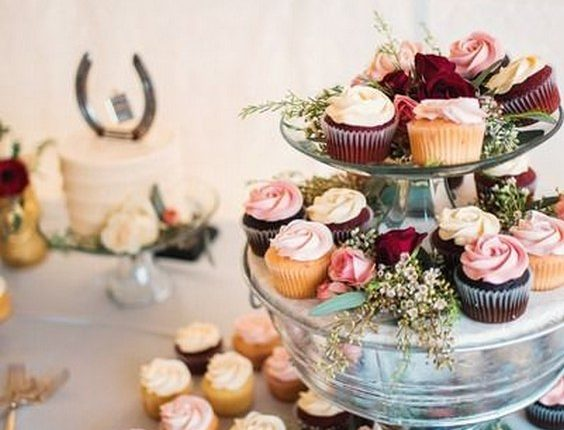 Wedding cupcake display- assorted cupcakes with ivory + pink frosting on clear tower with greenery + flowers
