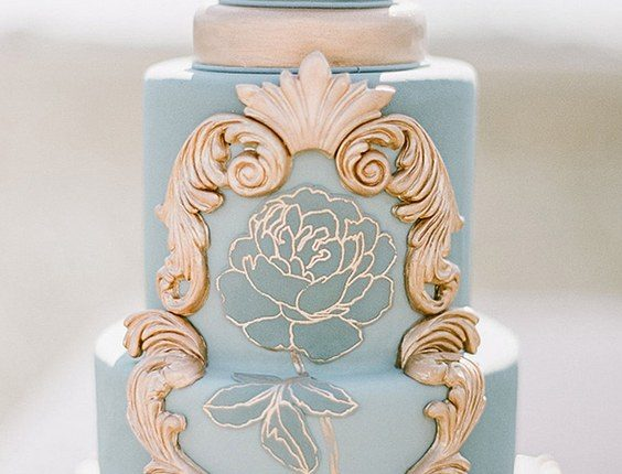 blue wedding cake with golden ornaments and rose