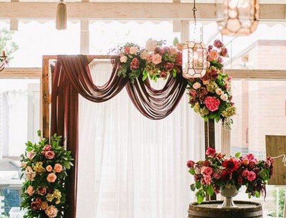 burgundy, blush, or gray draping wedding arch