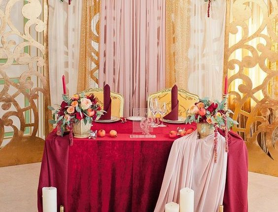 burgundy color tones and floral greenery wedding head table