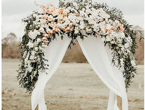 floral wedding arch with white and peach flowers, greens and draped fabric