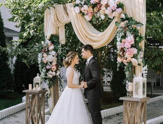 rustic peach fabric and latern wedding arch
