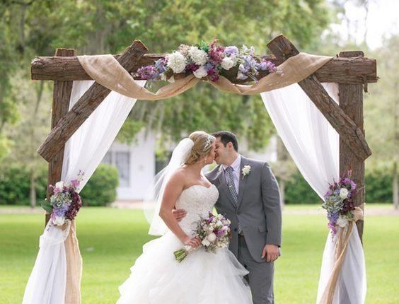 rustic tree stump and burlap outdoor wedding arch
