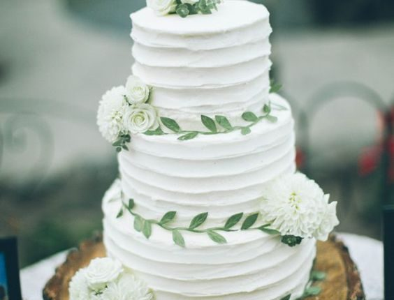rustic white buttercream wedding cake with greenery sugar leaves
