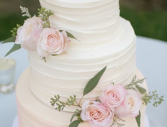 rustic white buttercream wedding cake with pink flwoers