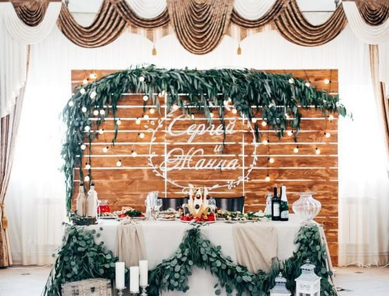 rustic wooden pallet wedding backdrop and sweetheart table with greenery garland