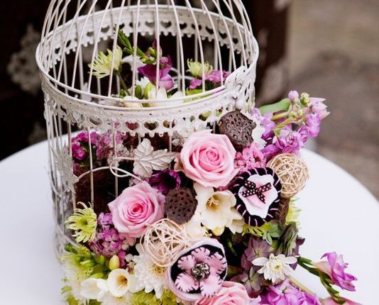 vintage birdcage and purple flowers wedding decor