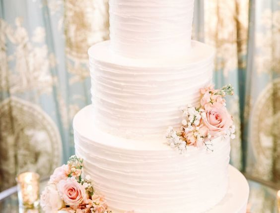 white buttercream wedding cake with pink peach roses
