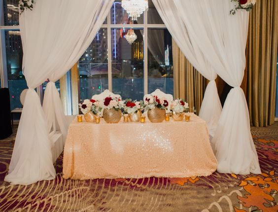 Sweetheart table under beautiful arch with lush floral garland