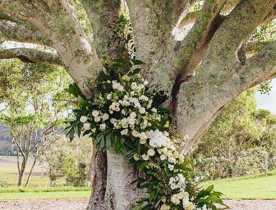 rustic backyard wedding decoration tall tall tree decorated with green and white flowers mondo floral designs