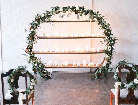 indoor candles and greenery wedding wreath backdrop