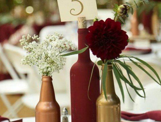 Gold and burgundy wine bottle centerpiece on wood round
