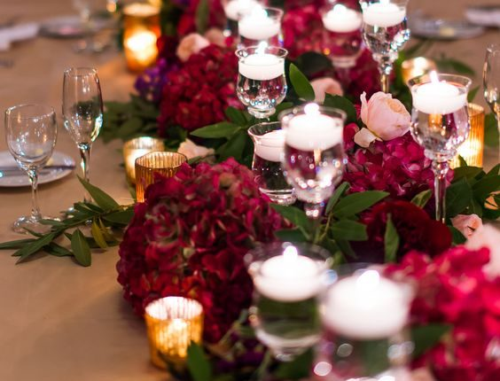 burgundy flowers and floating candles wedding centerpiece