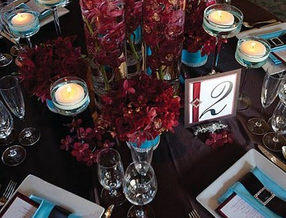 submerged burgundy orchids with floating candles wedding centerpiece
